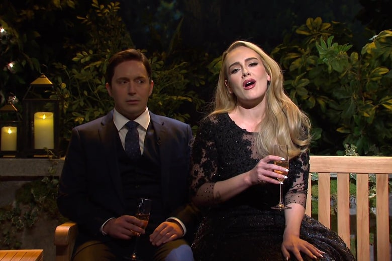 Beck Bennett and Adele sit on a wooden bench on a candlelit patio. Adele is singing while Bennett gives her a side-eyed look.
