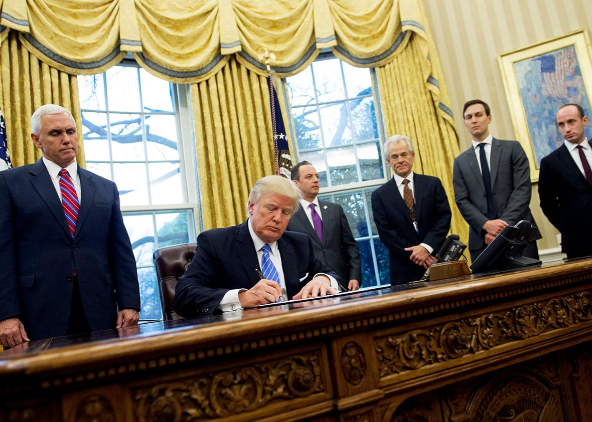 US President Donald Trump signs an executive order in the Oval Office of the White House in Washington, DC, January 23, 2017.