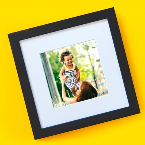 A framed photo of a woman tossing a joyous child.