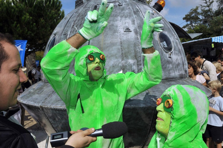 Two people in green outfits and face paint in front of a fake flying saucer