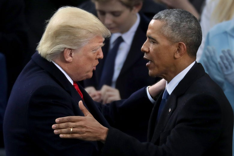 Trump and Obama touch each other's shoulders while speaking face to face.