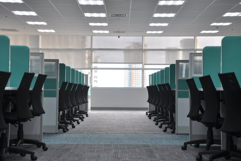 Two empty rows of cubicles and desk chairs