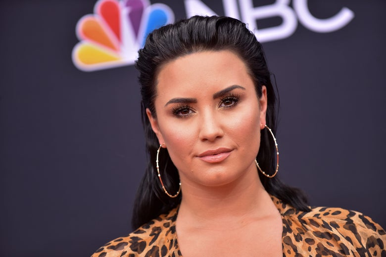 Demi Lovato on a red carpet in front of the NBC logo. She wears hoop earrings and leopard print.