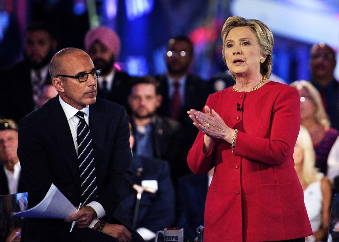 """Matt Lauer, co-host of """"The Today Show,"""" listens as Democratic presidential nominee Hillary Clinton speaks during a veterans forum at the air and space museum aboard the aircraft carrier USS Intrepid on September 7, 2016 in New York, New York."""