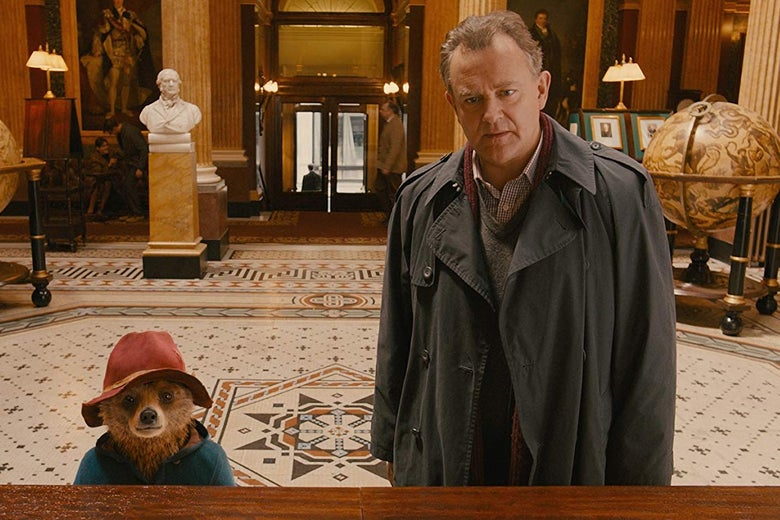 A small brown wear wearing a red hat and a man, Hugh Bonneville, wearing a trenchcoat. They stand in front of a desk in an elaborate lobby with a marble bust and a large globe in the background.