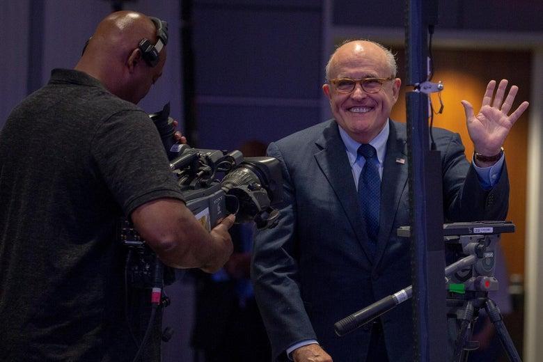 Rudy Giuliani waves as a camera crew films him.