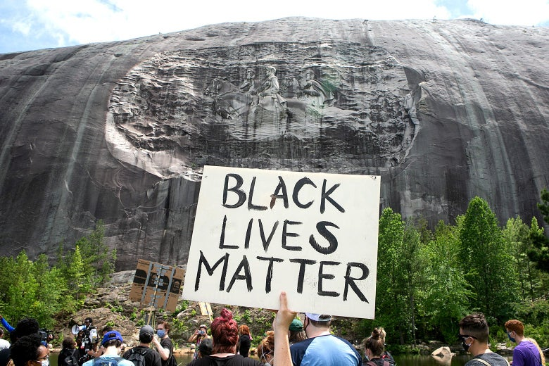 Someone holds up a sign that says Black Lives Matter in front of the massive bas-relief on Stone Mountain.