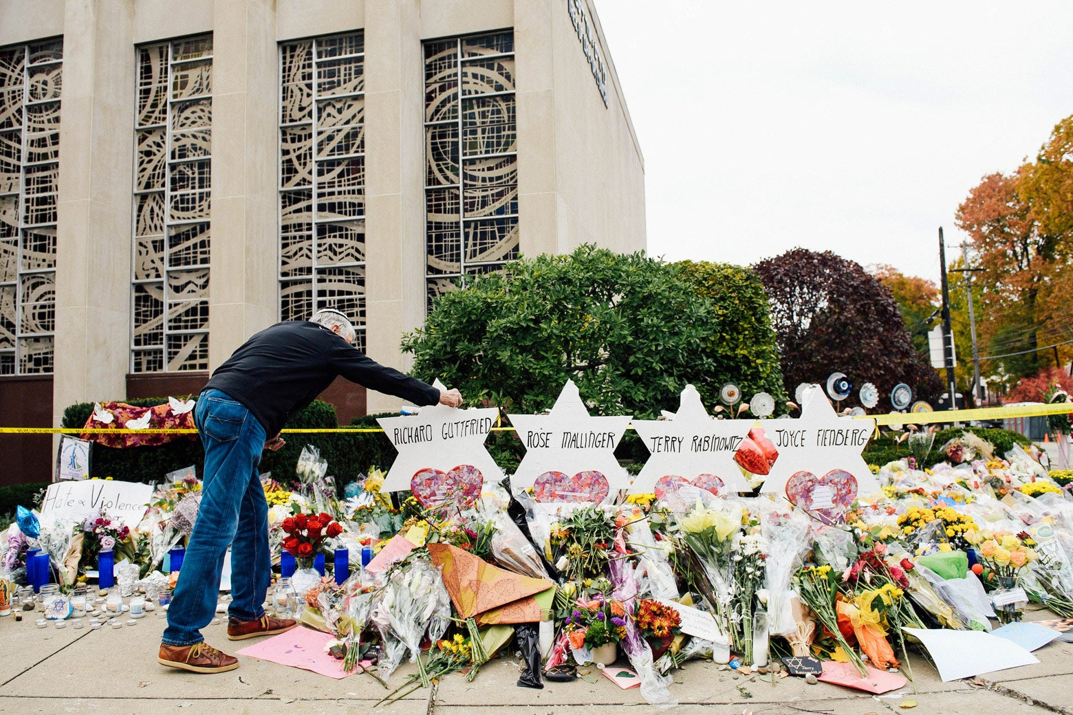 A man adjusts a marker for a shooting victim at the memorial outside Tree of Life synagogue. The memorial is full of flowers.