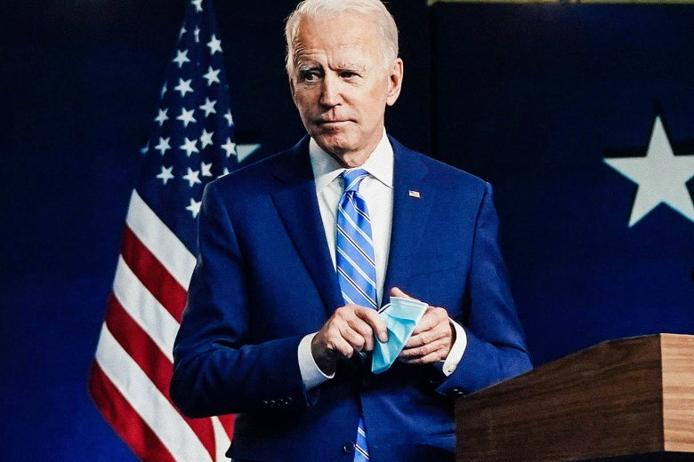 Biden, holding a surgical mask, walks away from a lectern, with an American flag in the background