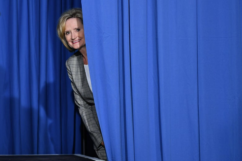 Sen. Cindy Hyde-Smith peaks out from behind a curtain before a rally.