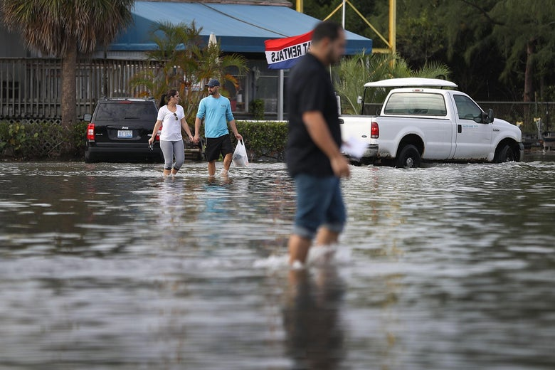 NORTH MIAMI, FL - NOVEMBER 14:  Yaneisy Duenas (L) and Ferando Sanudo walk through the flooded parking lot to their boat at the Haulover Marine Center on November 14, 2016 in North Miami, Florida. The flood waters are caused by the combination of the lunar orbit which causes seasonal high tides, also known as a King tide, and what some scientists believe is rising sea levels due to climate change.  (Photo by Joe Raedle/Getty Images)