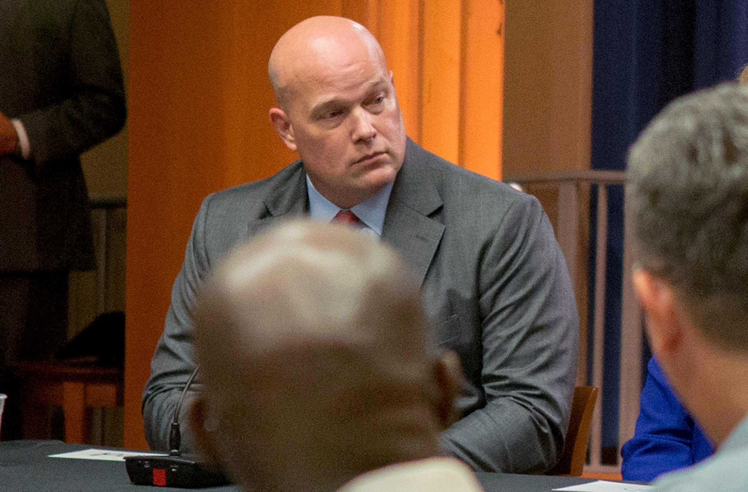 Whitaker sitting at a table. He's bald. The view of him is partially blocked by a different bald guy.