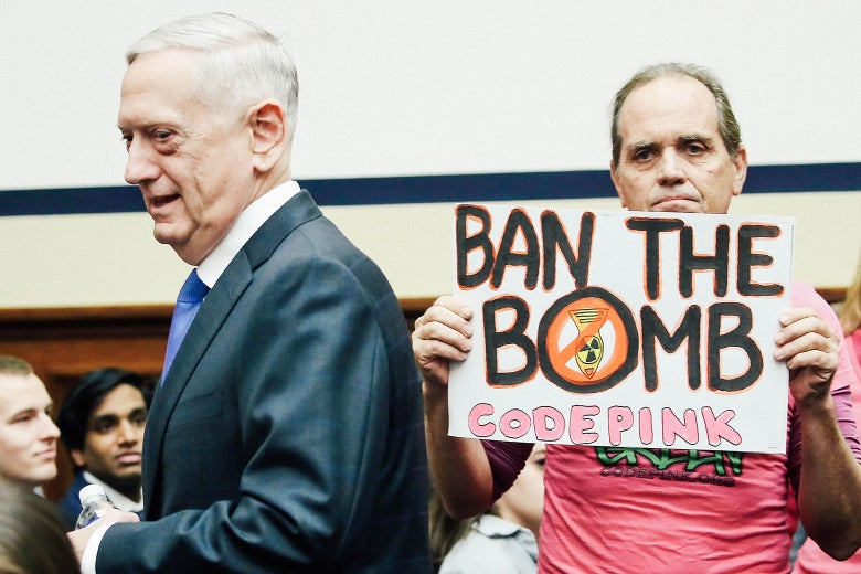 "Defense Secretary Jim Mattis walks past a protester holding a sign that says, ""BAN THE BOMB. CODE PINK."""