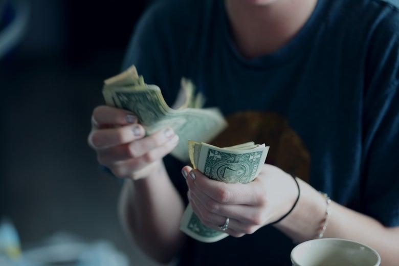 A woman wearing a T-shirt counts dollar bills.