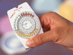 Woman holding birth control pills.