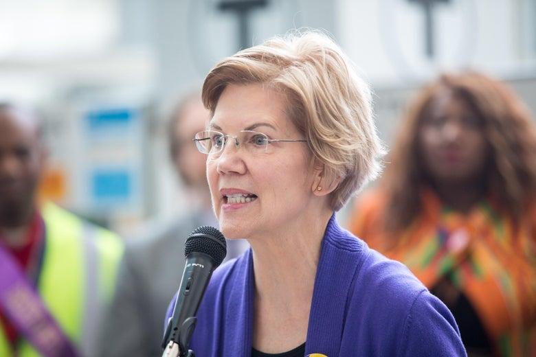 Warren, wearing a purple sweater, speaks in front of a crowd of airport employees.
