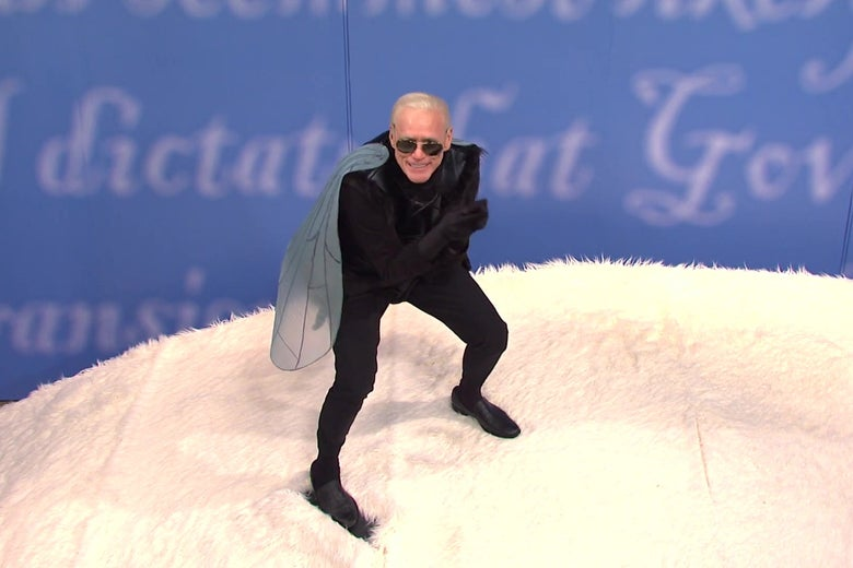 Jim Carrey as Joe Biden, wearing a fly costume, atop a giant white fuzzy floor meant to evoke Mike Pence's hair.