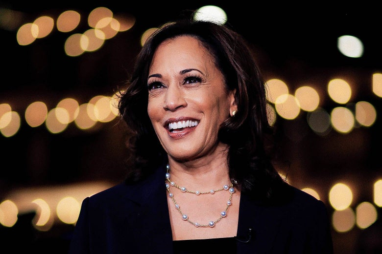 Kamala Harris, in a dark suit set against a dark background accented with lights.