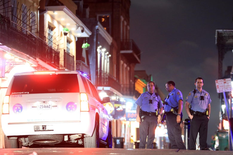 Police officers stand next to a police SUV on Bourbon Street