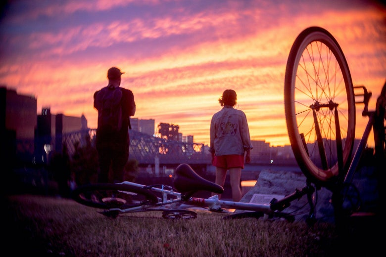 A bicycle is seen lying on the ground. Two people stand in front of it.