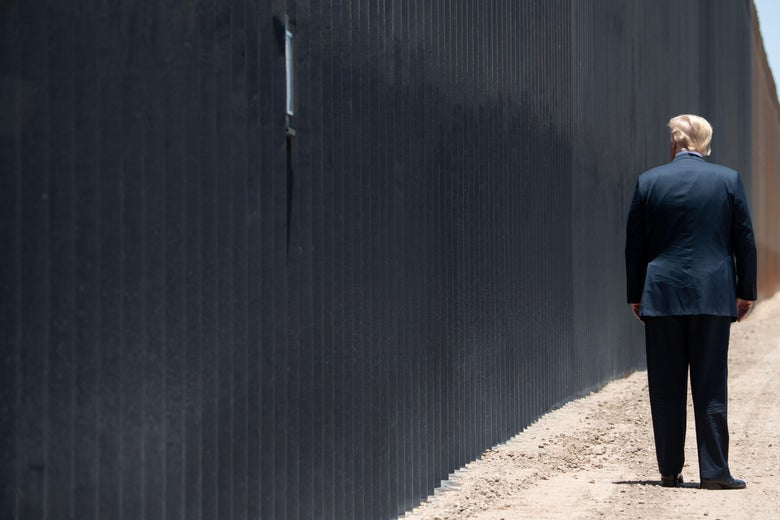Trump, photographed from behind, standing near the border wall.