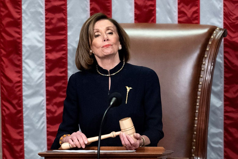 Nancy Pelosi holds a gavel while standing at a podium in front of an American flag.