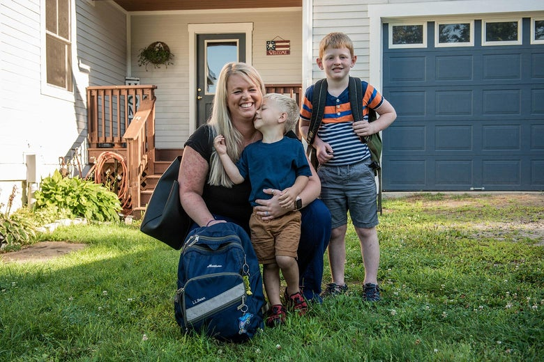 Heather smiles with her two boys in a yard outside a house