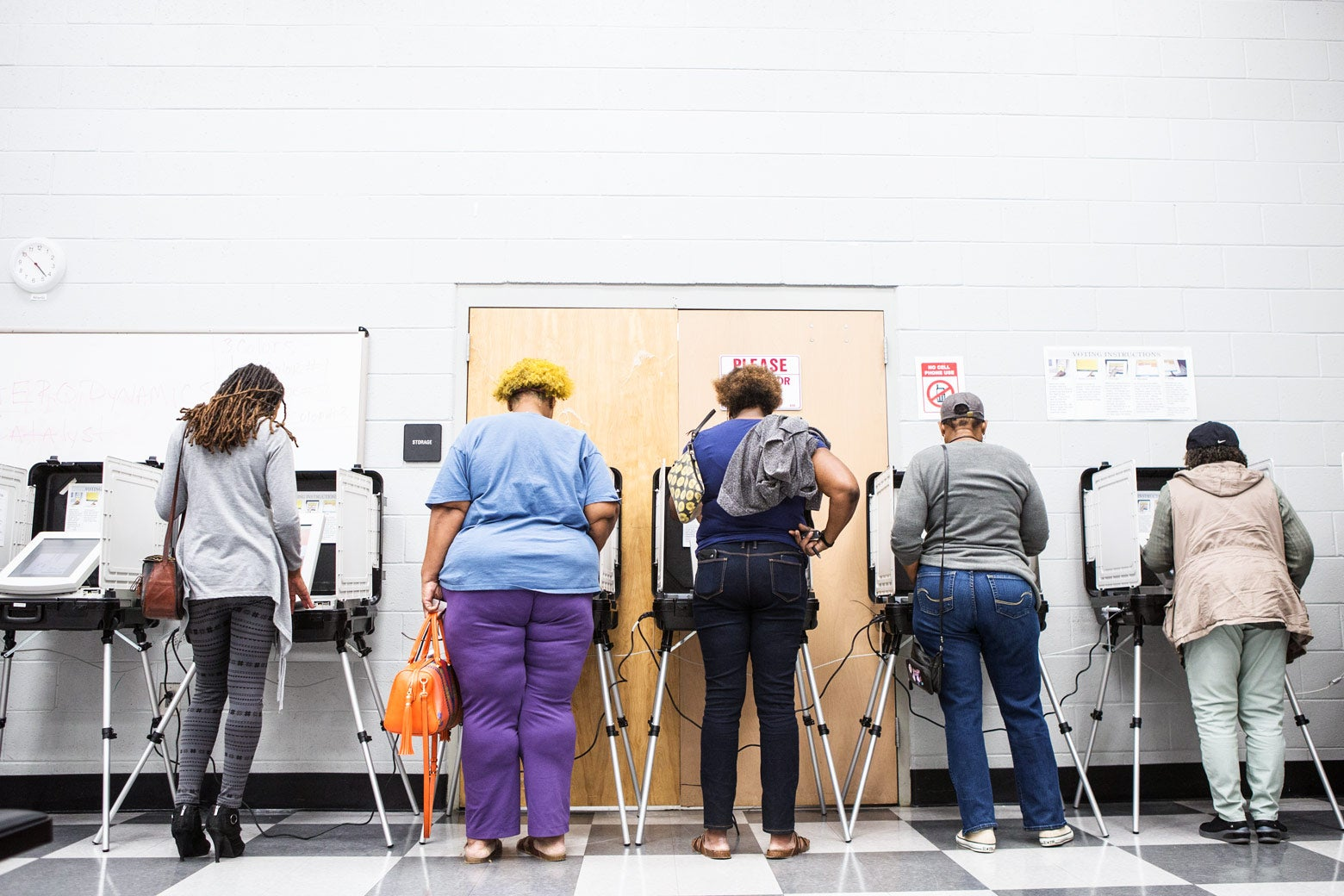 A row of voters at voting machines.