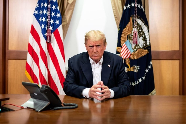 Trump, seated at a conference room table inside the Walter Reed Medical Center, looks into the camera.