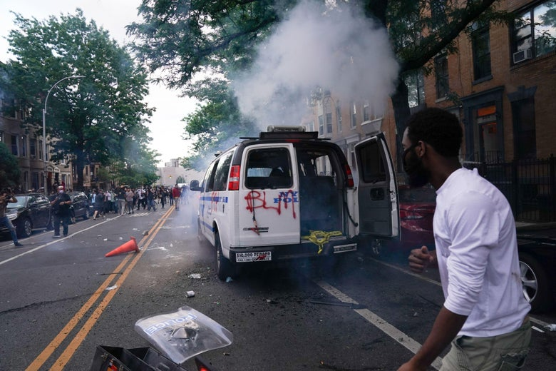 A man runs by an NYPD police van on fire during a demonstration against the killing of George Floyd by Minneapolis police on Memorial Day on May 30, 2020 in the Borough of Brooklyn in New York.