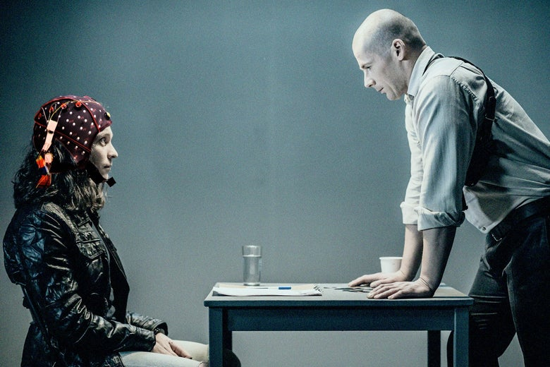 A woman sits in front of a table wearing a helmet with electrodes, while a man stands on the other side, his hands on the table, looming.