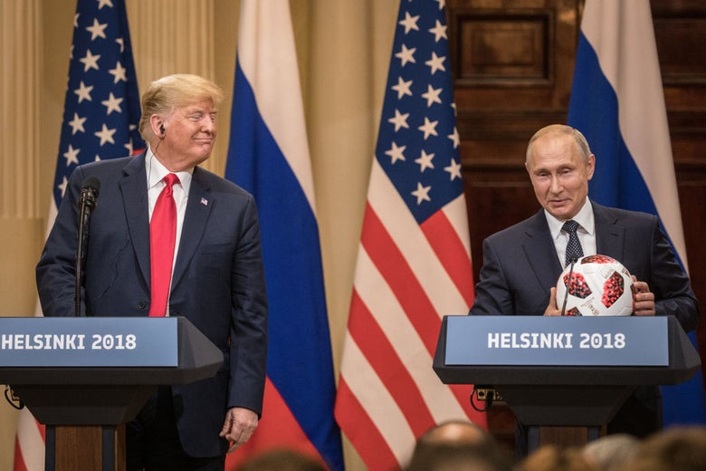 Trump smiles towards Putin, who is holding a souvenir soccer ball, as they stand at lecterns.