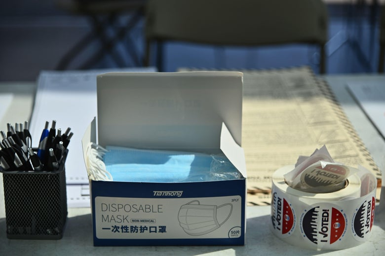 "A container of pens, a box of disposable face masks, and a roll of ""I Voted"" stickers on a table"