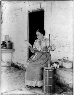Woman churning milk to butter, 1897.