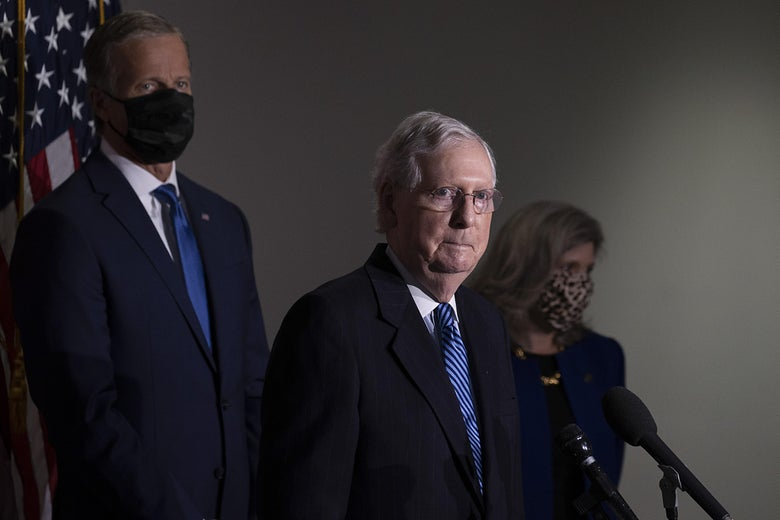 Mitch McConnell speaks at a mic with two people flanking him