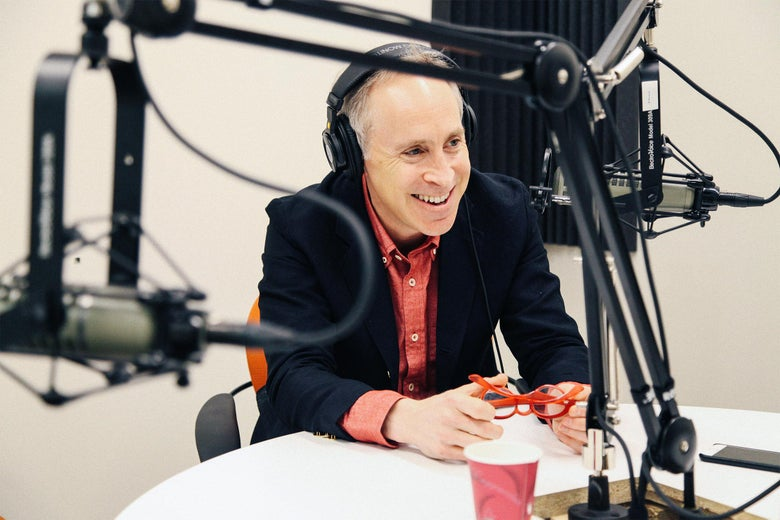 Jacob Weisberg sits in a podcast studio, smiling.