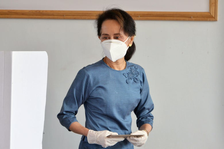 Aung San Suu Kyi, wearing a white mask and white gloves, holds a ballot