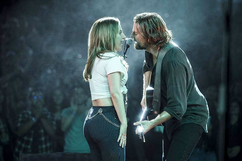 In a scene from A Star Is Born, Lady Gaga and Bradley Cooper sing into a mic onstage.