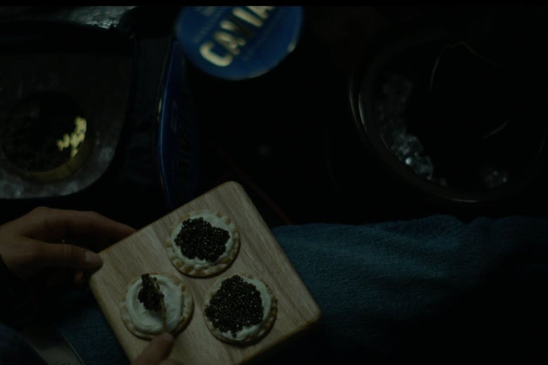 Caviar-topped crackers on a serving board