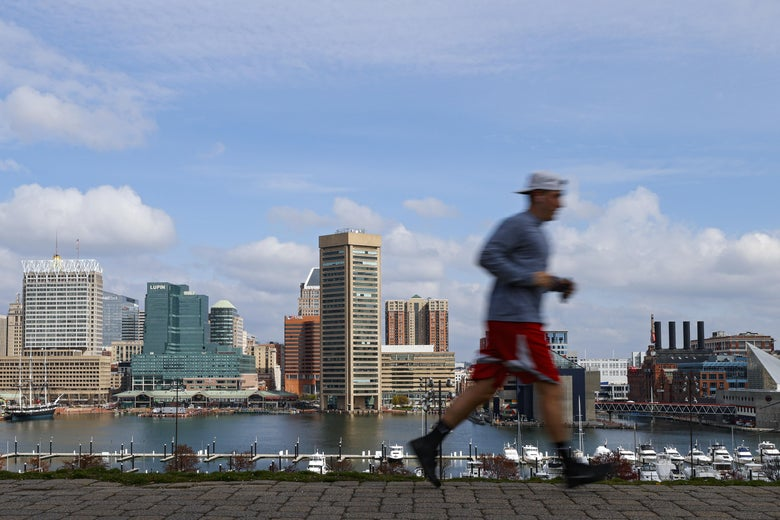 A man runs on a walkway near the water, with the downtown Baltimore skyline in the background