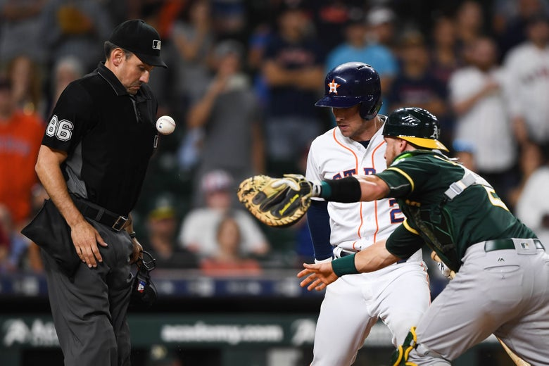 A's catcher Jonathan Lucroy lunges for a ball he's just dropped while attempting to tag Astros batter Alex Bregman as it bounces off the home-plate umpire.