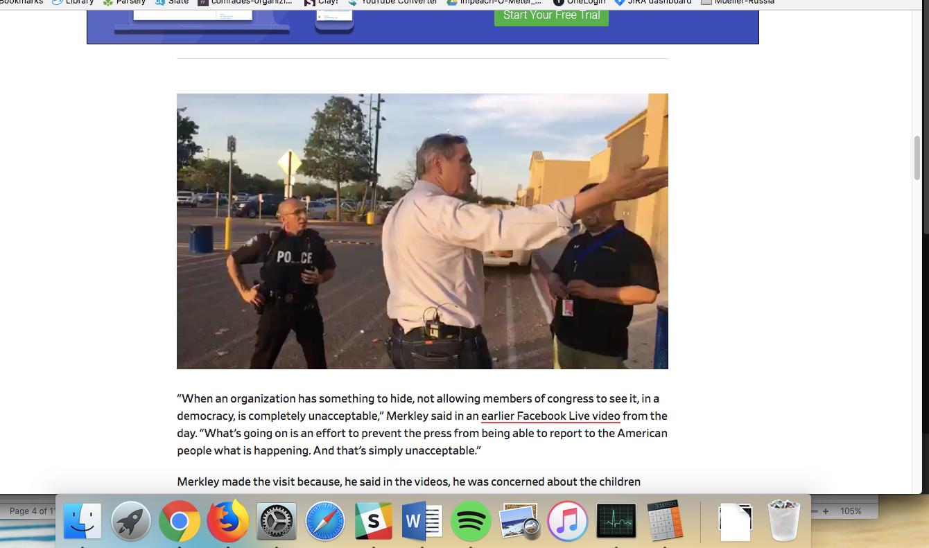 Merkley gestures toward the facility as a police officer looks on.