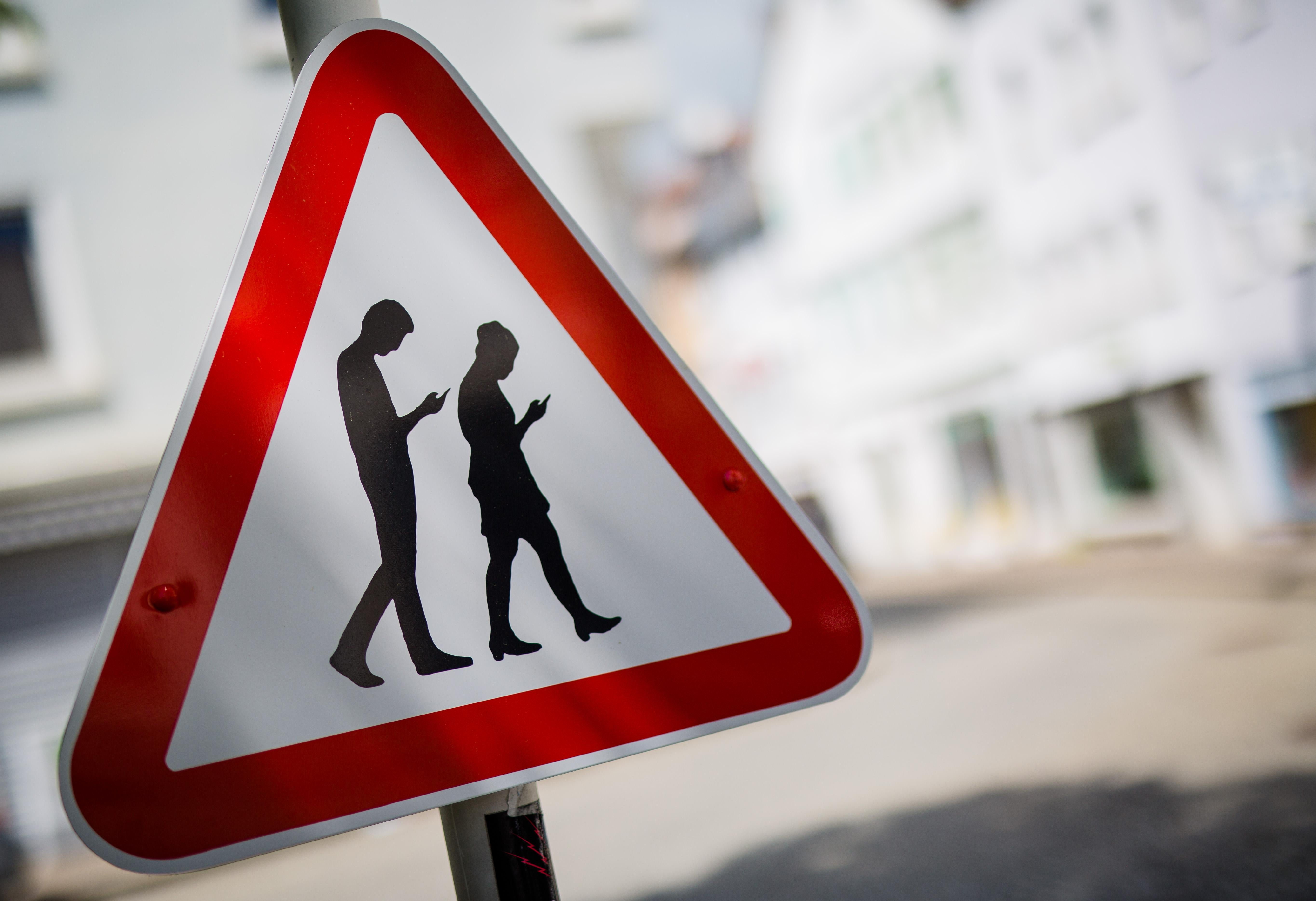 A modified caution sign that depicts two people walking while looking down at their phones.
