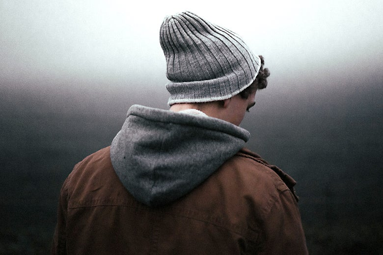 A teenaged boy with a coat and knit hat facing away from the camera.