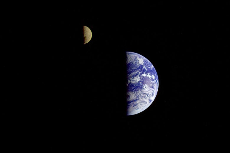 A black sky with half of Earth and half of the moon both in view near each other.