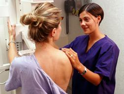 Nurse positioning patient for mammogram.