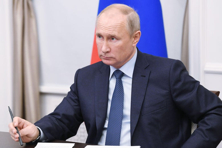 Putin sitting at a desk holding a pen, with a Russian flag behind him