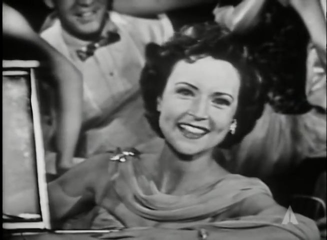 A young Betty White behind the wheel of a 1954 Oldsmobile Starfire 98.