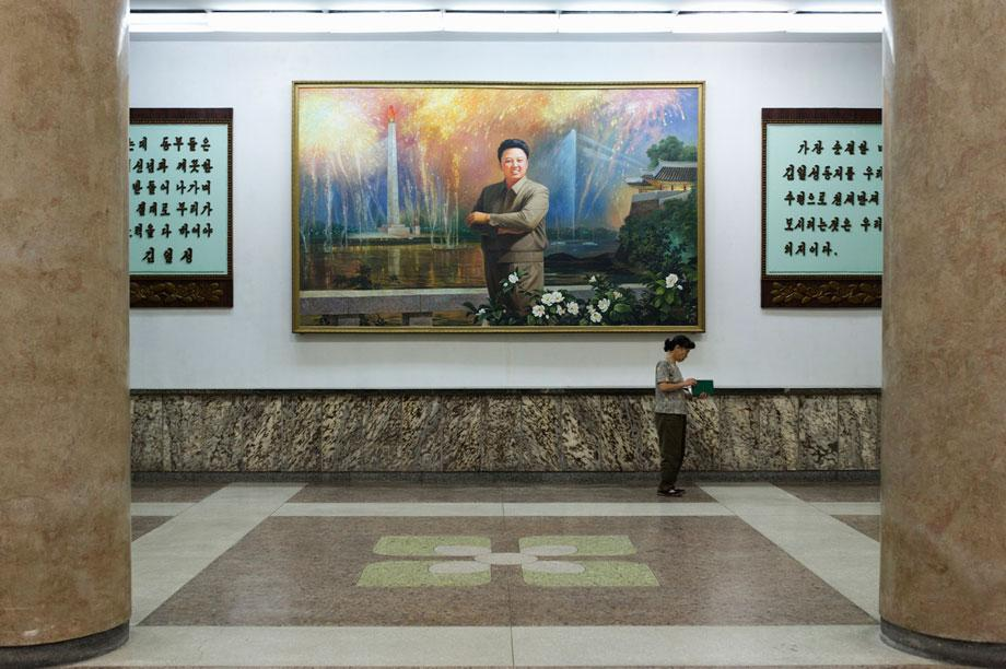Woman reading a book under a Kim Jong-il painting Grand People's Study House, North Koreas biggest library and educational centre.  It has a total floor space of 100,000m2 and 600 rooms. Foreign publications are available only with special permission.