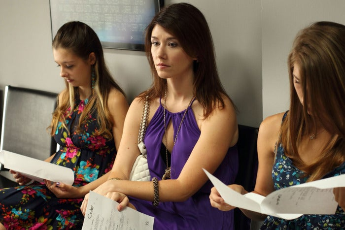 Jewel Staite sits, wearing a purple blouse, sits on a black bench next to two other women, all three holding pieces of paper stapled together